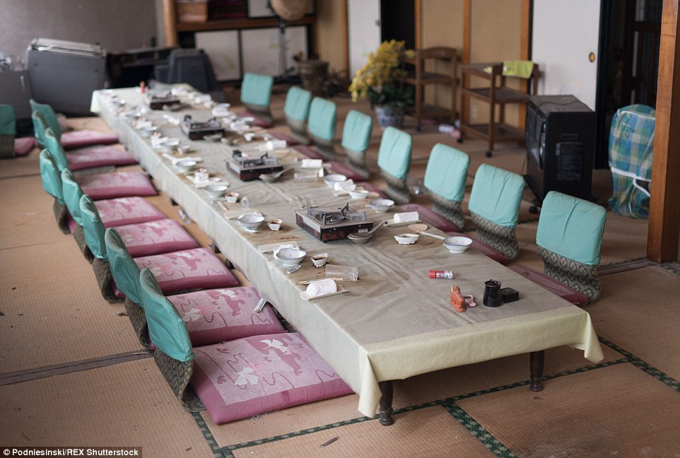 A dining table and seats, complete with bowls and portable cookers ready for food to be prepared, lie untouched