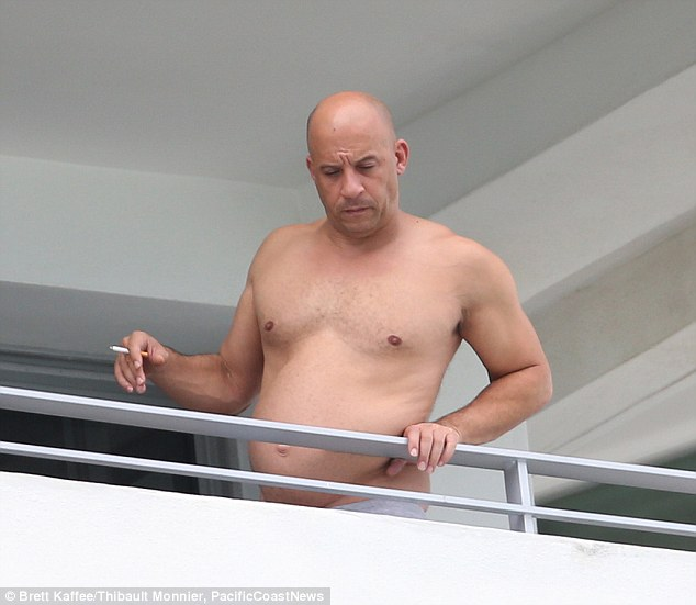 Enjoying a cheeky smoke: Vin Diesel took his shirt off while basking in the Florida humidity on the balcony of the Shore Club, showcasing his famous physique, on Tuesday