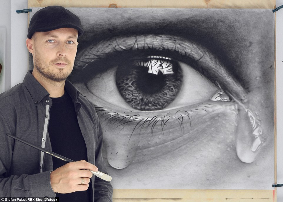 Unique view: Mr Pabst poses next to one of his pictures, using both the photorealistic style he has adopted for portraits and the 3D technique he has perfected to create the tears