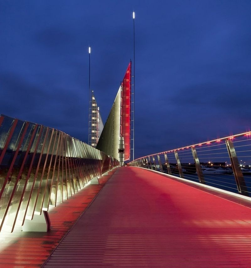 The pedestrian walkway is lit in bright red while the sails are white.