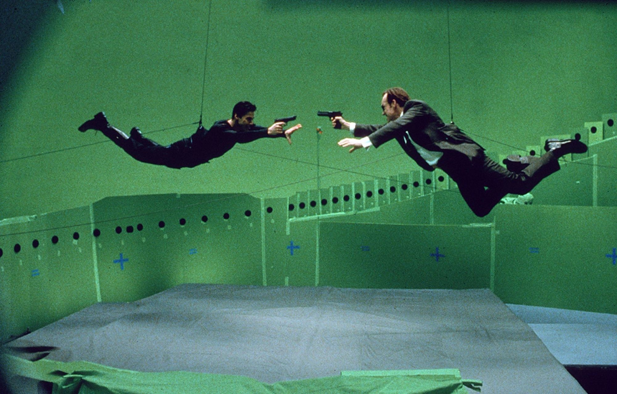 Keanu Reeves and Hugo Weaving shooting at each other in The Matrix.