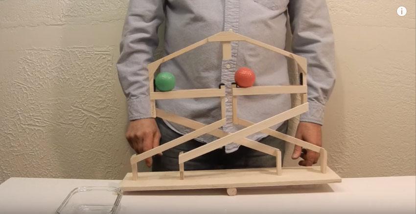 他把一顆綠色和橘色的球放在這個「特殊的蹺蹺板上」,接著當他一推後...所以網友全都猜不出當中永動奧祕!