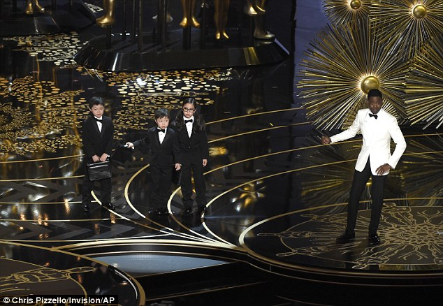 Rock invited three young Asian children (pictured) on to the stage at the Oscars and introduced them as 'PricewaterhouseCoopers accountants'