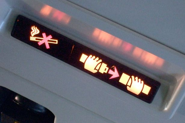 A display showing the 'fasten your seatbelt' sign and the 'no smoking' sign