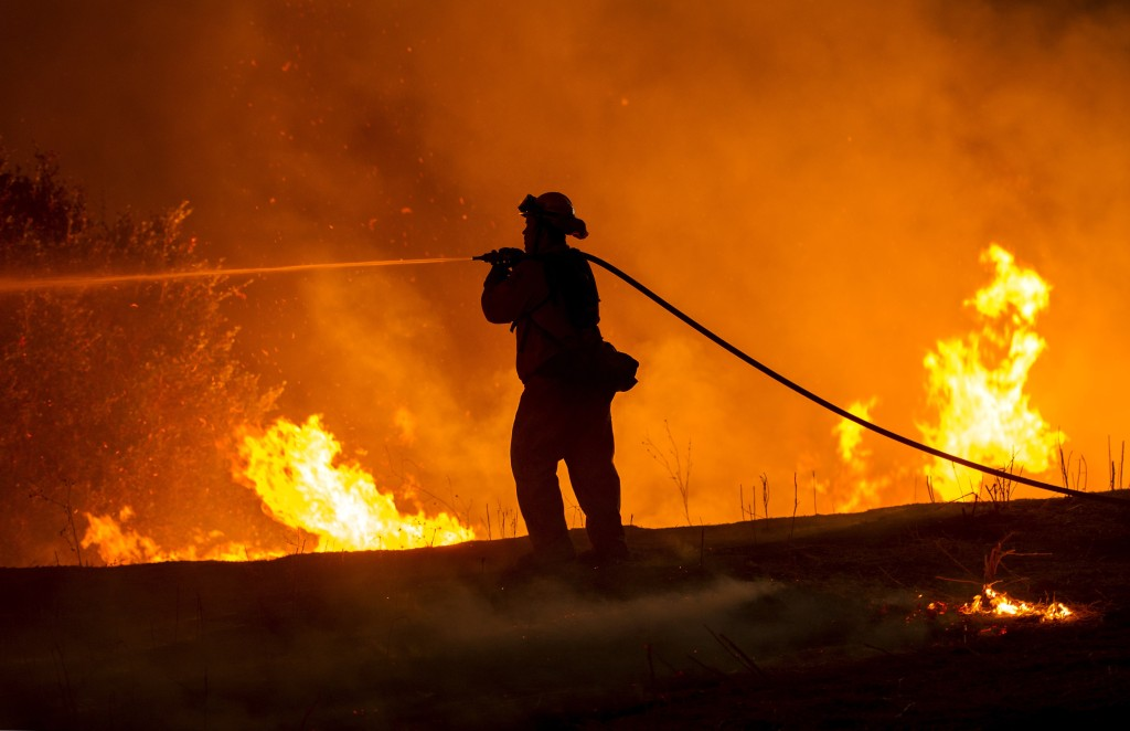 Firefighter Joe Darr douses flames of the Rocky fire along Highway 20 near Clearlake, California on August 2, 2015. Thousands of firefighters battled raging wildfires on August 2 in drought-parched California, where officials evacuated entire neighborhoods and closed miles of highway in the path of the inferno, which has claimed at least one life. AFP PHOTO / JOSH EDELSON        (Photo credit should read Josh Edelson/AFP/Getty Images)