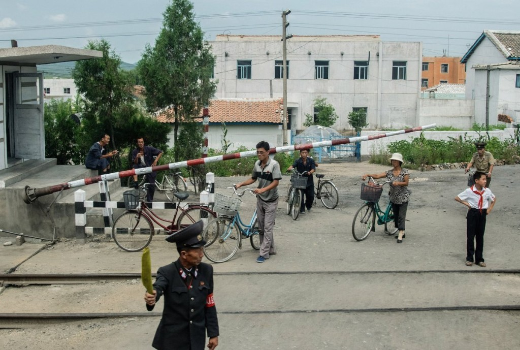 many-people-rode-bicycles-as-seen-at-a-railway-crossing-en-route