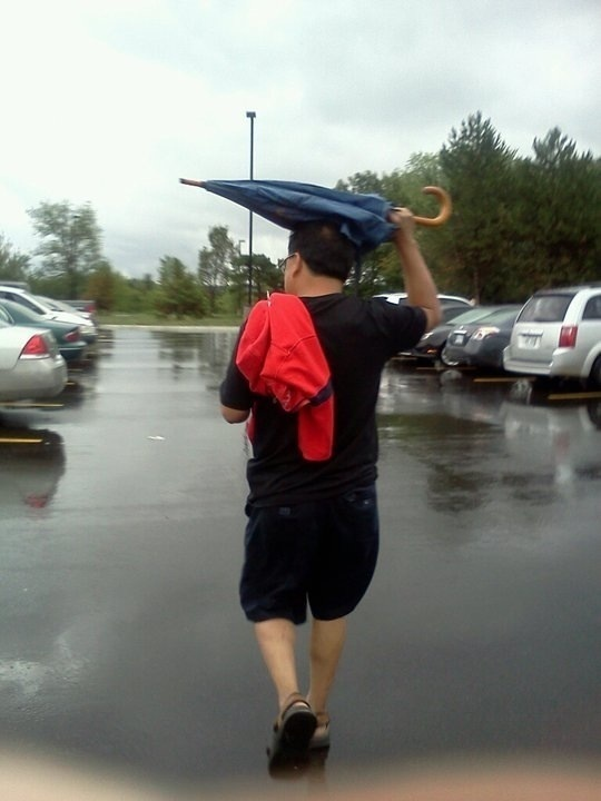 He keeps getting wet despite the umbrella.