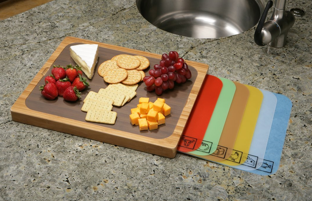 A cutting board with built-in storage space for a variety of mats.