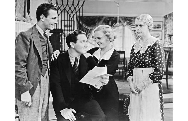 """ca. 1934 --- Cast members from the 1934 film The Show-Off pose together on the movie set. Left to right: Henry Wadsworth as Joe Fisher, Spencer Tracy as J. Aubrey Piper, Madge Evans as Amy Fisher Piper, and Clara Blandick as Mrs. """"Ma"""" Fisher. --- Image by © John Springer Collection/CORBIS"""