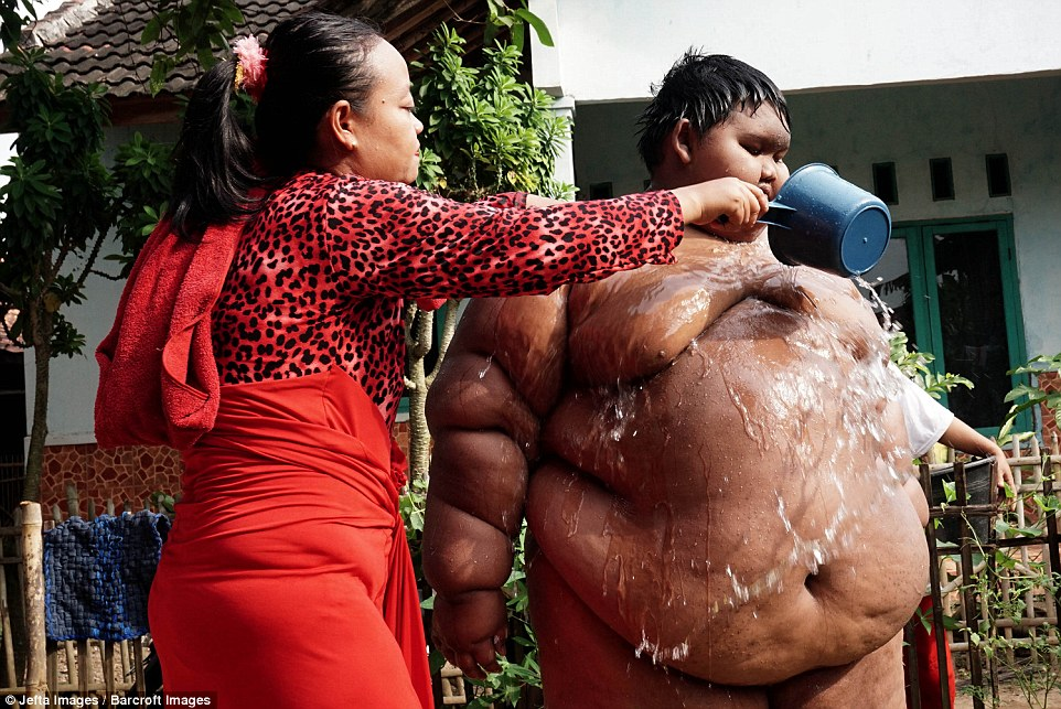 Arya's mother assists him to bathe in a small pool out the front of their home in Indonesia