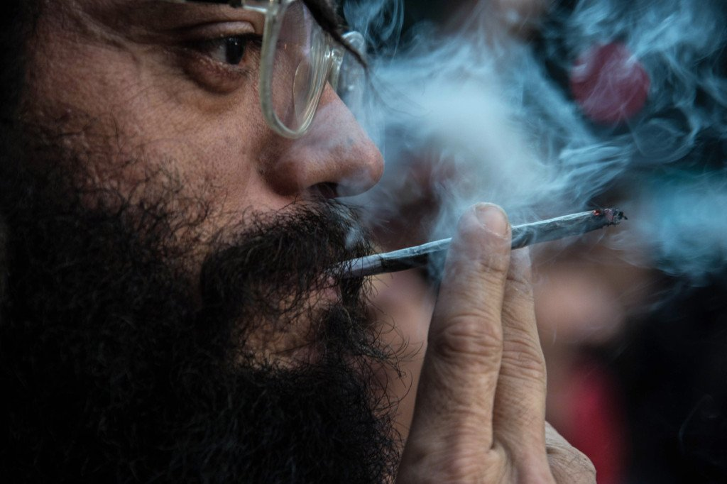 A demonstrator smokes a joint during a march calling for the legalization of marijuana along Paulista Avenue in Sao Paulo, Brazil, on May 14, 2016. / AFP / NELSON ALMEIDA        (Photo credit should read NELSON ALMEIDA/AFP/Getty Images)