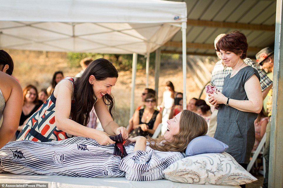 Amanda Friedland, left, adjusts her friend Betsy Davis's sash as she lays on a bed during her 'Right To Die Party' in Ojai,surrounded by friends and family
