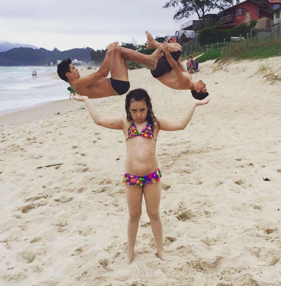 This picture of a little girl holding up two flipping Brazilian gymnasts: