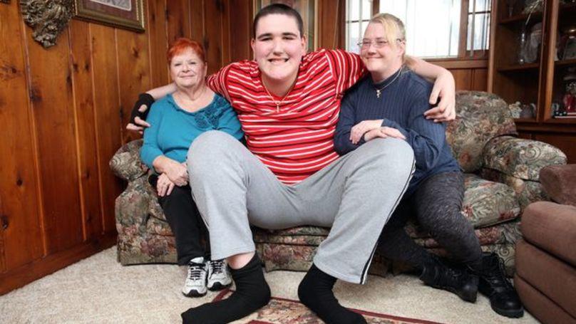 這名19歲就長到233公分的巨人族青年「一年長高15公分」且還在繼續。站起來的照片根本是視覺錯視圖!