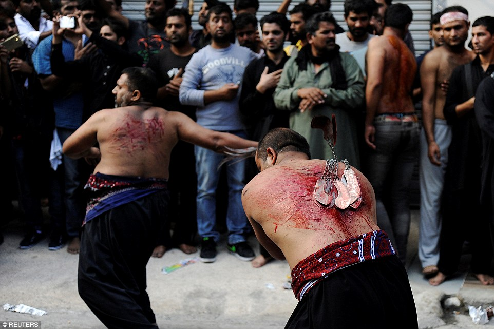 Two Muslims use the over-sized razorblades to puncture huge gashes in their backs in the streets of Piraeus, Greece