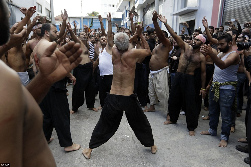 Massive crowds gather to take part and watch as a man prepares to launch knives into his back in the street