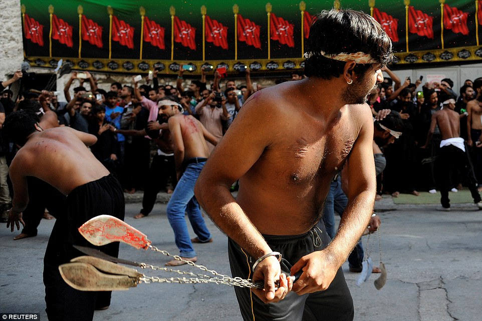 Bloodied knives are swung in Greek streets as a group of men slice themselves open - and the scars are evident