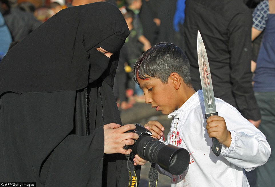 An Iraqi Shiite boy looks at his picture during the reenactment of the Battle of Karbala, as part of a parade in preparation for the peak of the mourning period of Ashura in Baghdad's northern district of Kadhimiya