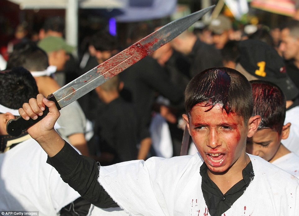 Iraqi Shiite boys take part in a self-flagellation procession during the reenactment of the Battle of Karbala, as part of a parade in preparation for the peak of the mourning period of Ashura