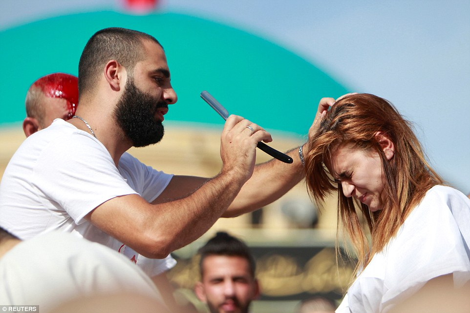 A woman braces herself as a Muslim man prepares to draw blood from her scalp while a second man drenched in his own blood watches on