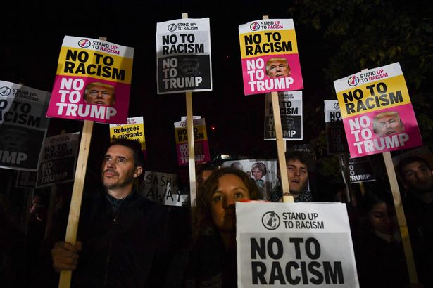 """Demonstrators hold placards that read """"No to racism, no to Trump"""" during a protest outside the US Embassy in London"""