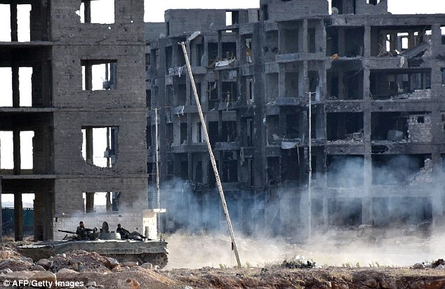Devastastion: Syrian pro-government forces were pictured driving past heavily damaged buildings in Aleppo's 1070 district yesterday after troops seized it from rebel fighters. Trump's election may empower Putin to continue his bombardment of the city