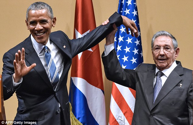 Allies: Cuban President Raul Castro, right, raises US President Barack Obama's hand during a meeting at the Revolution Palace in Havana in March, which marked a thaw in US-Cuba relations - a deal which Donald Trump has said he will back away from