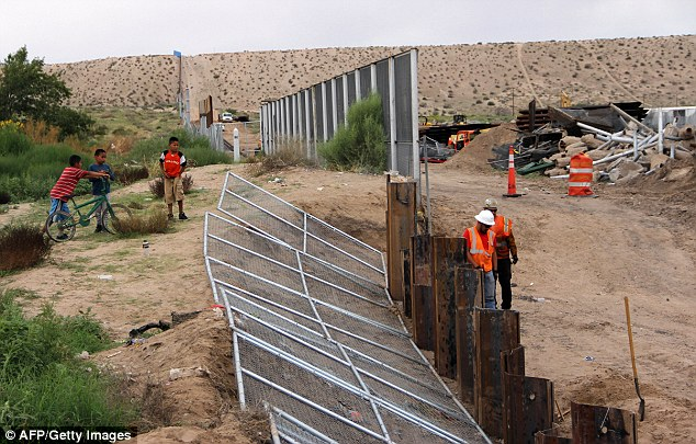 US workers replace fencing with a higher new metal wall along the border between Ciudad Juarez and Sunland Park, New Mexico.The obstacles to a 'Trump Wall', which Michael Burleigh believes will not be built, are actually rivers, lakes and Texan landowners