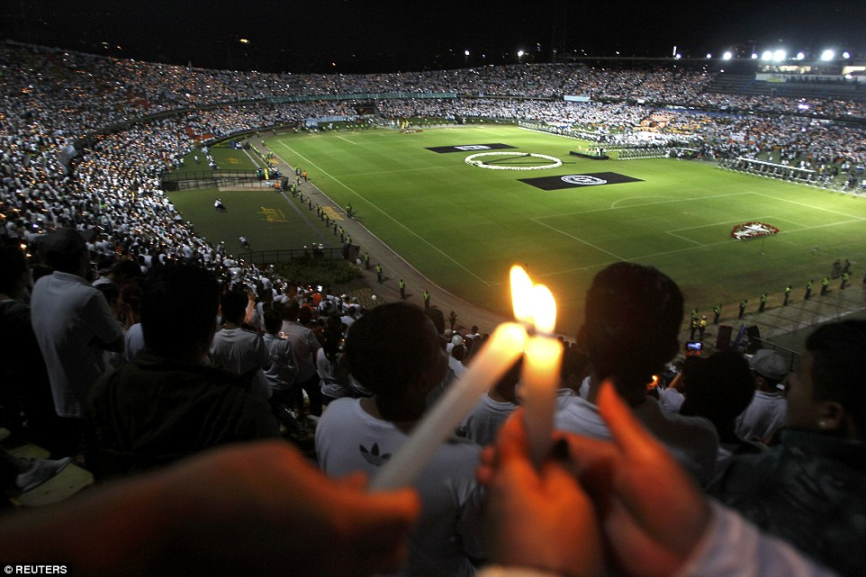 As the probe into the devastating crash continued, mourning soccer fans in Medellin and the southern Brazilian town of Chapeco, where the team is from, held simultaneous stadium tributes to the victims.Atletico Nacional fans are pictured holding candles as part of a tribute