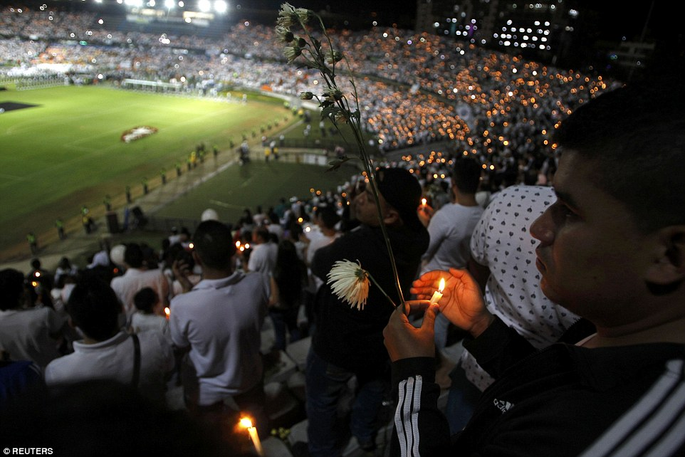 Fans of Atletico Nacional soccer club hold candles as they pay tribute to the players of Brazilian club Chapecoense killed in the recent airplane crash