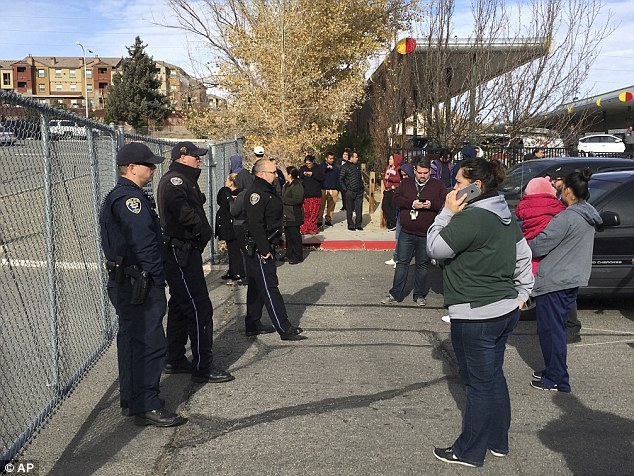 Parents wait outside Hug High School after the officer-involved shooting Wednesday