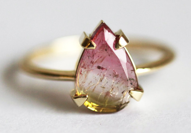 A watermelon tourmaline ring featuring what look like suspended magical particles.