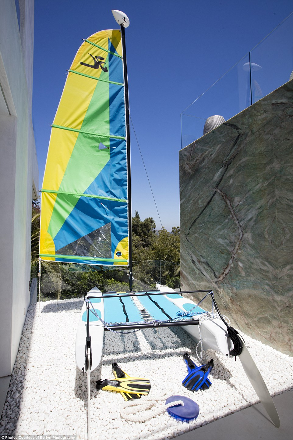 A Hobie Cat is displayed next to the infinity pool, in keeping with other nautical nuances scattered around the estate