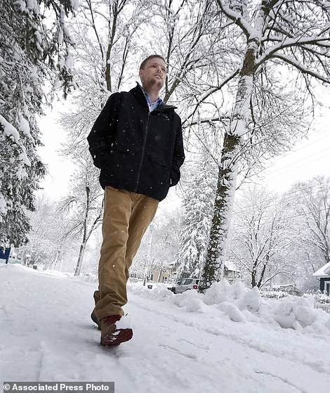 """In this Jan. 25, 2017, photo, face transplant recipient Andy Sandness walks to the Saint Marys Hospital campus at Mayo Clinic in Rochester, Min. Sandness can pinpoint the day he looked normal. About three months after the procedure, he was in an elevator with a little boy who glanced at him, then turned to his mother without appearing scared or saying anything. """"I knew then,"""" he says, """"that the surgery was a success."""" (AP Photo/Charlie Neibergall)"""