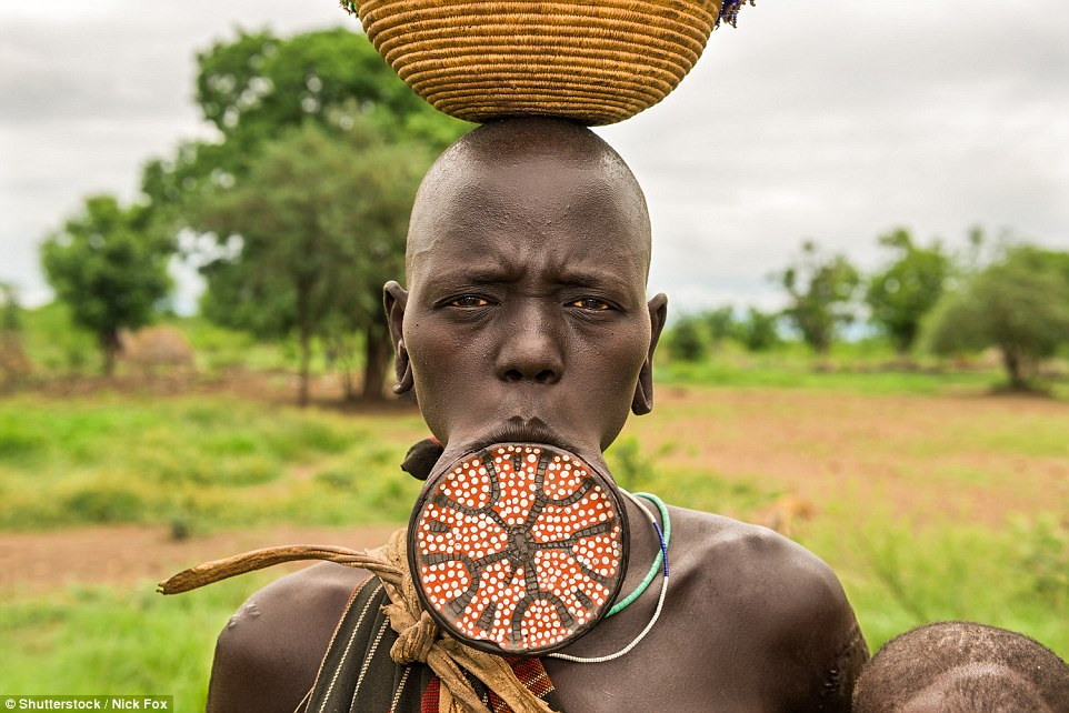 A woman from the African tribe of Mursi in Omo Valley, Ethiopia, displays her lip plate - an expression of female maturity and a signal that she is ready to bear children - achieved by stretching the piercing with discs of increasing size