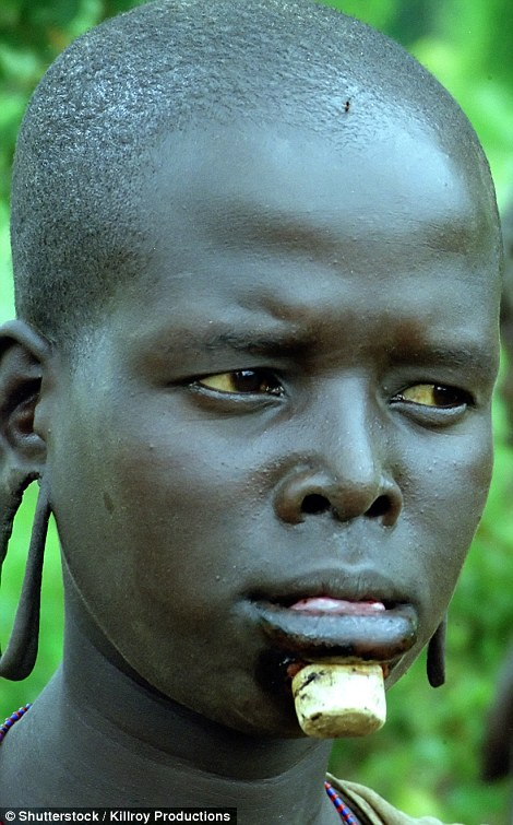 An African woman with stretched earlobes and a chunky lip piercing