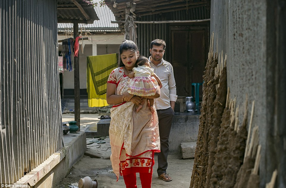 Meghla and Liton walk with their baby girl in the city of Khulna, Bangladesh. She gave birth two months ago