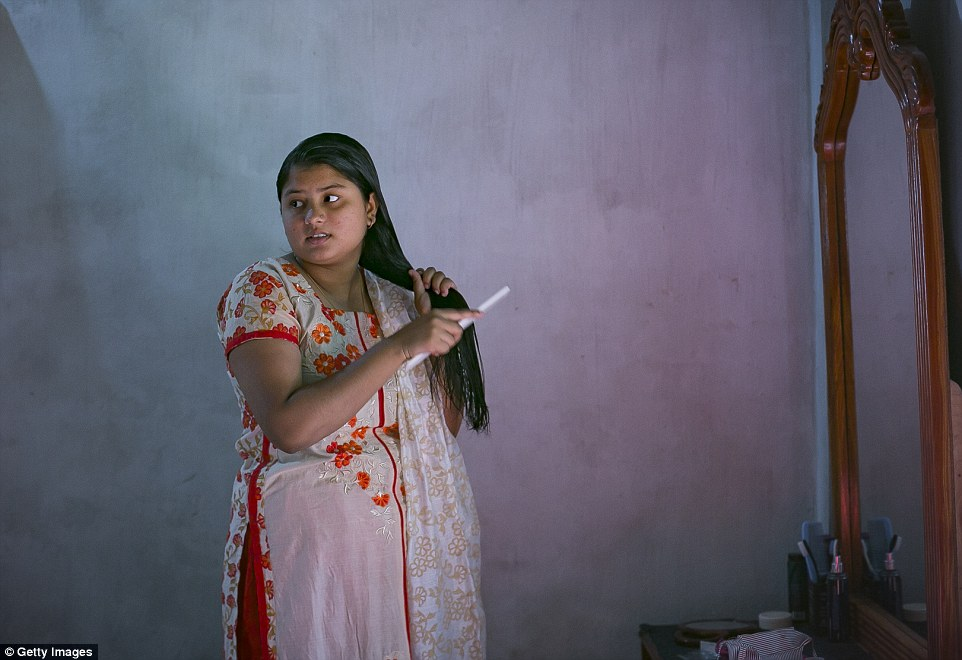 The young mother does her hair. 'If a girl is more than 20 and unmarried then she and her family are sexually harassed,' she says