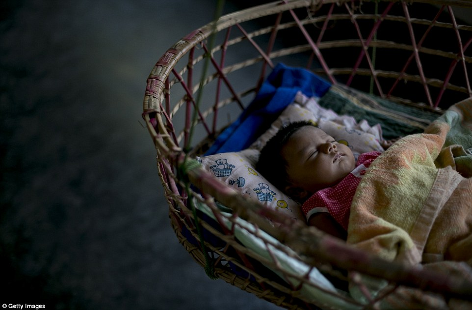Meghla's two-month-old baby sleeps in a cot. She is the latest female in a family full of under-age marriages