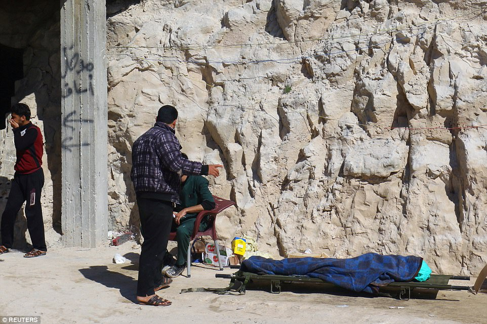 People stand near a dead body, after what rescue workers described as a suspected gas attack in the town of Khan Sheikhoun in rebel-held Idlib, Syria