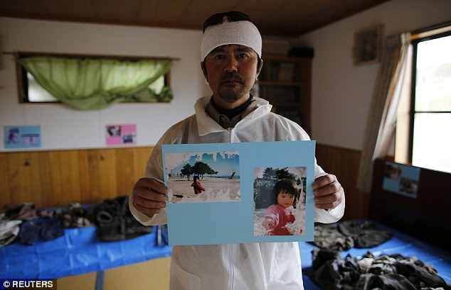 Mr Kimura holds up photos of his seven-year-old daughter who was swept away by the wall of water