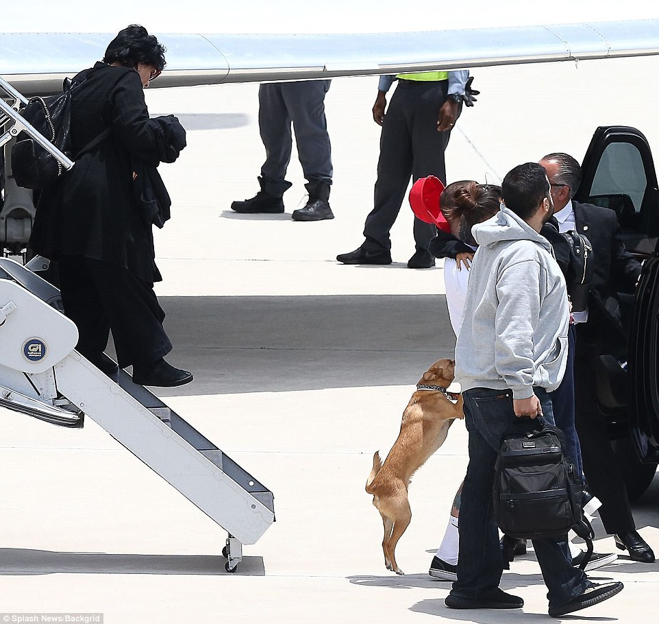 Long embrace: Ariana was carried to the SUV by Miller while her mother Joan made her way off the plane
