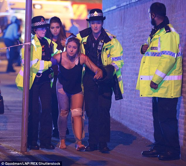 The masked jihadi, who sat with a sign which read 'Manchester 2017-05-02', was the latest ISIS sympathisers to celebrate the atrocity. Pictured: A victim is escorted from Manchester Arena
