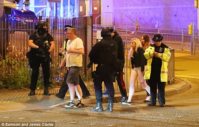 Two messages, posted four hours before the attack, appeared to predict the atrocity. Pictured: Terrified concert goers leave the venue