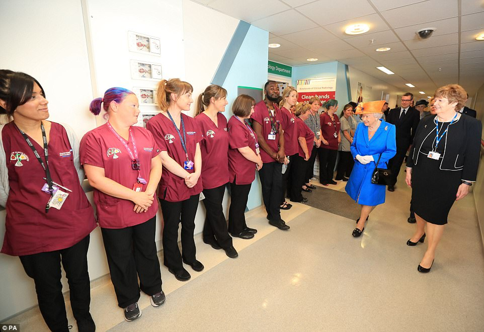 Proud: Staff lined the corridor as the Queen made her way through the building this morning, escorted byKathy Cowell, right Chairman of the Central Manchester University Hospital. She said the level of community spirit shown had been 'splendid'